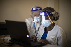 Instructor in mask and face shield oversees student in mask and face shield at computer