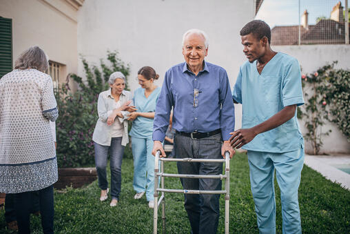 Nurse guiding elderly man with walker
