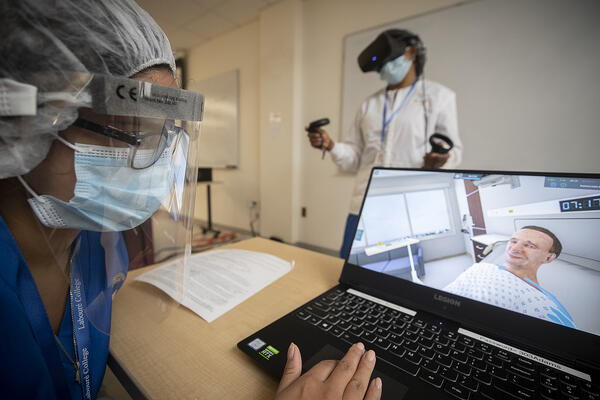 Nursing student in mask and face shield controls UbiSim virtual reality scenario while other student in mask stands with headset and hand controllers